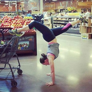 A woman in practical yoga clothes is doing a handstand in the middle of the fruit/veg aisle at market - one leg rests backwards on the shopping trolley while the other leg is fully extended elegantly forwards