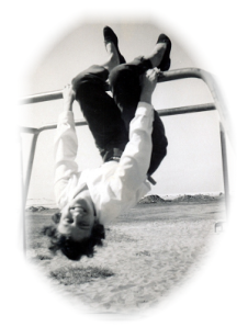 "black and white photo of a young woman with pale skin and short dark curly hair. She is hanging upside down by her knees from playground ""jungle bars"", laughing at the camera."