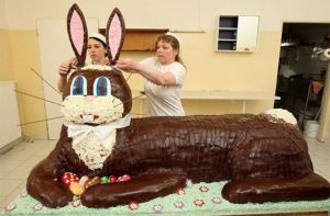 Two women placing ears on top of the head of an enormous chocolate Easter bunny.