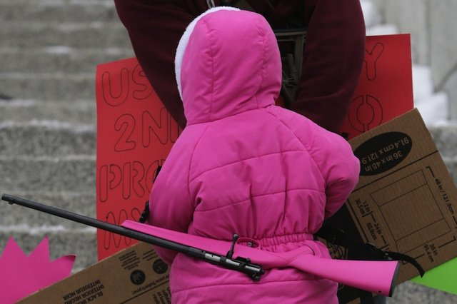 A very small child in a bright pink parka, viewed from behind, with a bright pink rifle slung on her back.