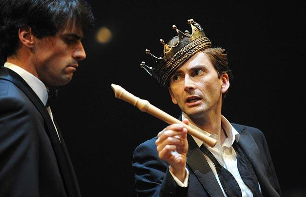 David Tennant in a suit, tie undone, with a crown tipped over one eye, offers his fellow player a recorder.
