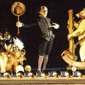 Puppet Shakespeare behind footlights, with a large basket full of props, and a cutout bear.