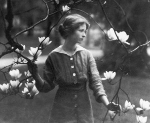 B&W photo of Millay as a young woman in a garden with magnolia blossom