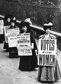 B&W photo of a row of Edwardian women holding signs demanding the vote.