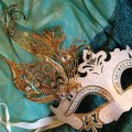 white and gold carnival mask on green silk
