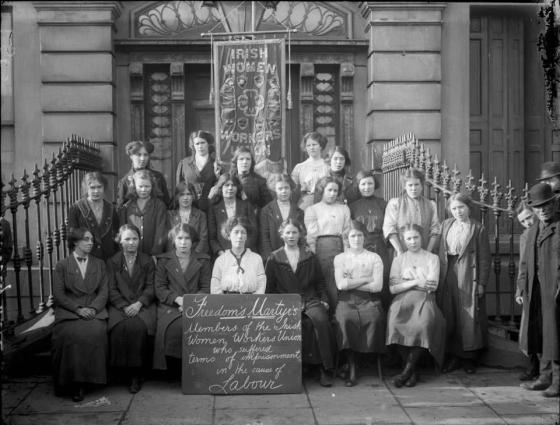 "B&W group of 20-something Irish women in early 20th century with a banner saying ""Irish Women Workers Union"" & chalkboard reading ""Freedom Martyrs""."