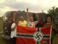 Four elderly but strong looking indigenous American women stand next to a van. They are holding a captured Nazi flag and cheering in preparation for burning it.