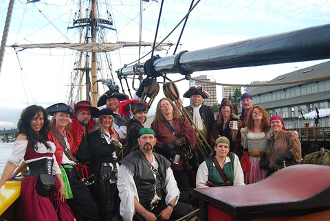 Group of men and women dressed as pirates in front of a tall ship.