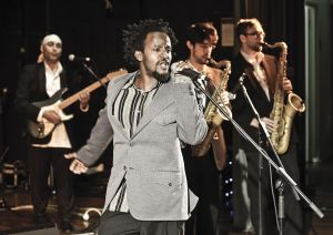 Black man at microphone with 3 men behind (2 tenor sax, 1 electric guitar).