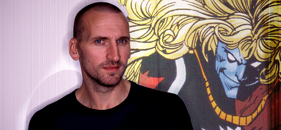 Christopher Eccleston stands in front of an original Marvel Comics illustration of Malekith the Accursed.