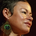Close up of face of Tina Harrod wearing peacock feather earring.