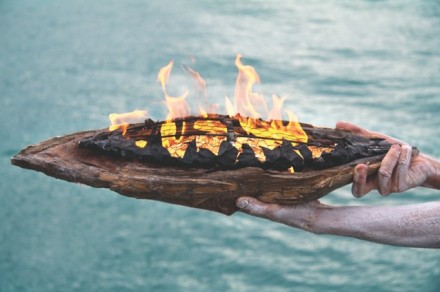 Ceremonial fire on bark plate held over water.