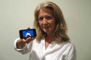 Sally Potter holds out a smartphone showing Jude Law.