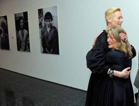 Tilda Swinton embraces the much shorter Sally Potter, in front of large photo portraits.