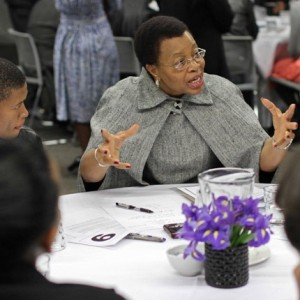 Graça Machel, in grey, speaking while seated at a table.