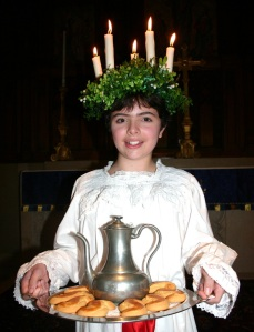 Girl of about 12 wearing crown of leaves and candles, carrying tray with pewter jug and buns.