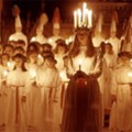 Group of girls holding candles, one at the front wearing a candle crown.