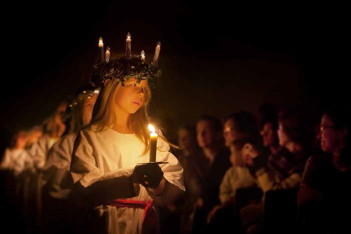 Young blonde girl wearing candle crown and carrying candle, with others behind her.