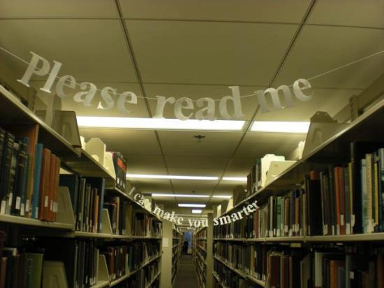 "Library shelves with a banner saying ""please read me"" strung between them."
