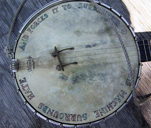 A well worn banjo body with faded rainbow text around the edge