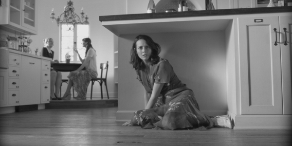 Move still, B&W, Acker hides under a kitchen bench, while two women talk in the background.