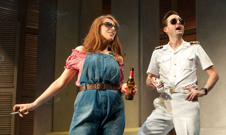 Tate in overalls, smoking, Tennant in naval whites, both with sunglasses.