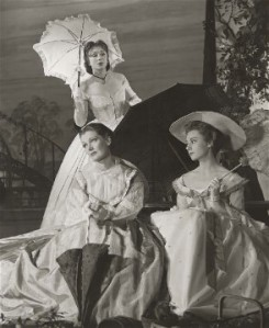 B&W of three women in C19th costume with parasols.