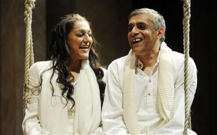 Middle-aged Indian woman and man wearing white sitting on a swing together, laughing.