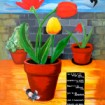 Poster art of beautiful flowering plants in terracotta pots on a balcony with a blue sky background: birds are swooping and a small mouse at the base of a flowerpoint looks at the viewer.