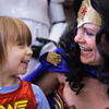 Woman in Wonder Woman costume laughs with child in WW shirt.