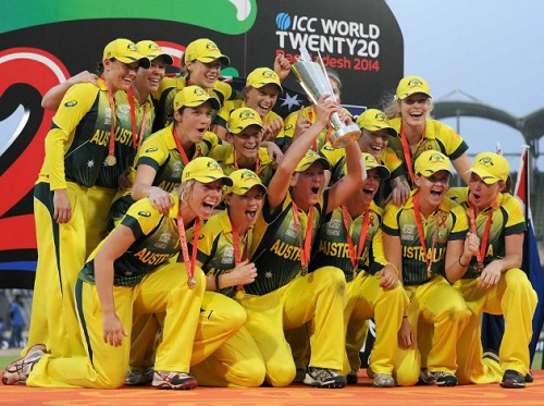 A group of jubilant sportswomen in the Australian national colours of green and gold pose for a photo with a championship trophy