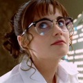 Zooey Deschanel in lab coat and glasses.