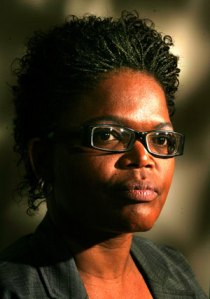 Head and shoulders portrait of black woman with glasses.
