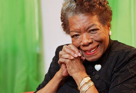 Head and shoulders of Maya Angelou in black dress, hands clasped.