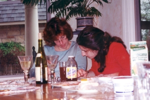 Middle-aged and young woman bent over work at a home table.