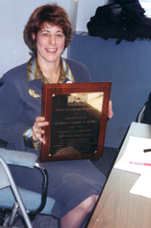 Dr Brodsky seated, holding a plaque.