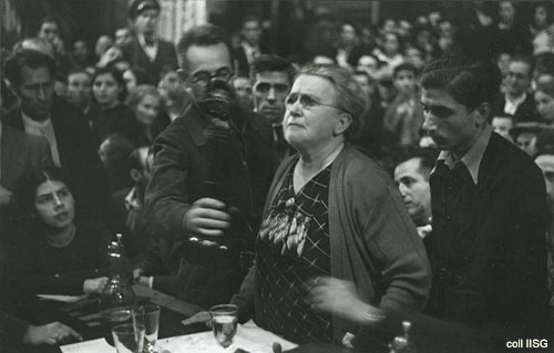 B&W Elderly woman in spectacles standing at a table with microphone, surrounded by seated people.