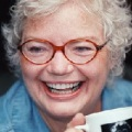 A middle aged pale skinned woman laughing unabashedly, holding a mug
