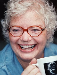 A pale skinned woman with white hair laughing unabashedly, holding a mug