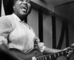 Black woman in white blouse singing, with electric guitar.
