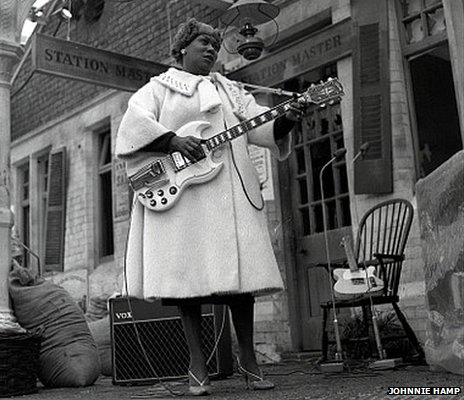 B&W of large black woman in fluffy 1960s coat playing a white electric guitar.