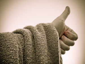 Photograph of a towel draped over an arm, with a thumb up to hitch a ride