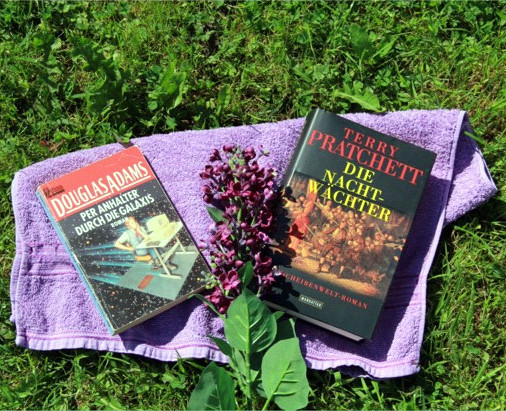 Photograph of German editions of The Hitch Hikers Guide to the Galaxy and Night Watch, together with a lilac towl and a sprig of lilac