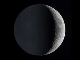 a photograph of Earth's moon showing a brightly sunlit crescent contrasted against the finally earthlit rest of the surface