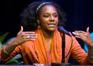 Young, black woman in orange speaking at microphone.