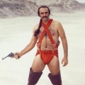 Sean Connery starring in the movie Zardoz. He is wearing some sort of orange nappy/bandolier with thigh-high black boots.