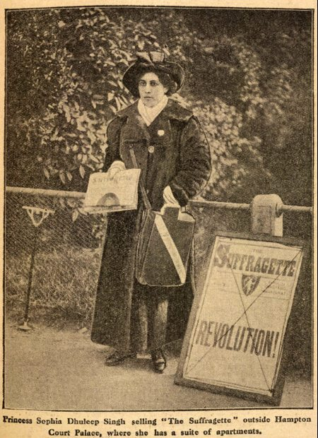 "Newspaper clipping showing woman in Edwardian dress selling newspaper next to a sign reading ""Suffragette Revolution!"""