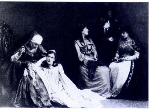 B&W early C20th photo of three women and two men in Orientalist costume.