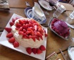 A table with a Xmas summer dessert feast: pavlova with strawberries and a berry sorbet pudding