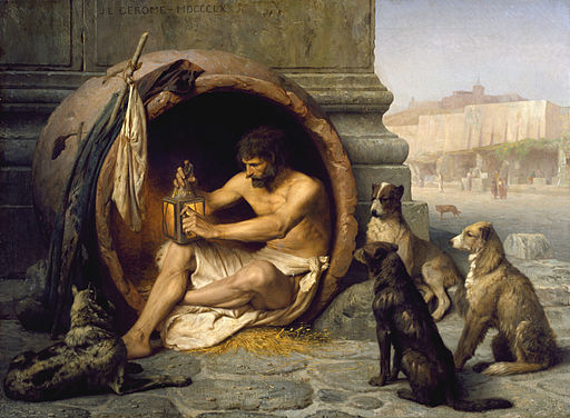 """The Greek philosopher Diogenes (404-323 BC) is seated in his abode, the earthenware tub, in the Metroon, Athens, lighting the lamp in daylight with which he was to search for an honest man. His companions were dogs that also served as emblems of his """"Cynic"""" (Greek: """"kynikos,"""" dog-like) philosophy, which emphasized an austere existence."""